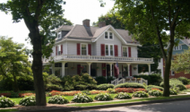 Photo of historic home with large, well-manicured yard in front